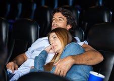 Älska hållande ögonen på film för par i teater Royaltyfri Bild