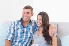 Älska hållande ögonen på TV för par på soffan Royaltyfria Bilder