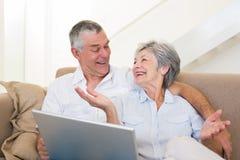 Älska höga par med bärbara datorn på soffan Royaltyfria Foton