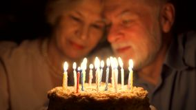 Älska höga par som firar årsdag med kakan som är hemmastadd i aftonen slående stearinljus ut