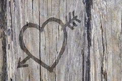 Älska hjärta- och pilgrafitti som snidas in i trä Royaltyfria Foton