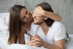 Älska kvinnabokslut mans ögon med händer som spelar i säng royaltyfri foto