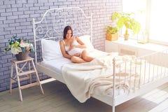 Älska kvinnan som trycker på hennes gravida buk på säng Arkivbilder