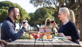 Älska lyckliga par som dricker vin och leende Arkivfoto