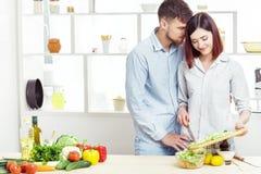Älska lyckliga par som förbereder sund sallad av nya grönsaker i kök Royaltyfria Bilder