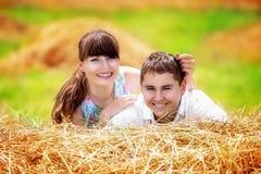 Älska lyckliga par som har gyckel i ett fält på en höstack Sommar Royaltyfri Bild