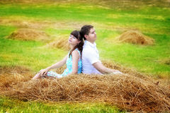Älska lyckliga par som har gyckel i ett fält på en höstack Sommar Royaltyfria Bilder