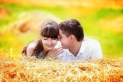 Älska lyckliga par som har gyckel i ett fält på en höstack Sommar Royaltyfri Fotografi