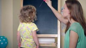 Älska mamman som hemma undervisar hennes brev för barnundervisningalfabet på kritabräde arkivfilmer