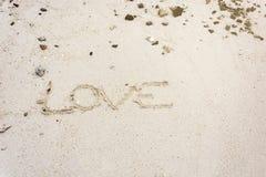 älska meddelandet som är skriftligt i sand, teckenförälskelse på sand Royaltyfri Bild