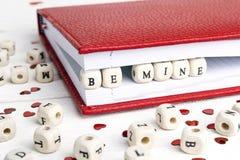 Älska meddelandet som är skriftligt i träkvarter i en anteckningsbok på vit w Royaltyfri Foto