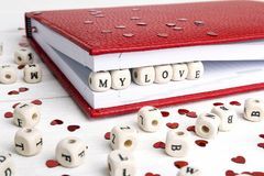 Älska meddelandet som är skriftligt i träkvarter i en anteckningsbok på vit w Arkivfoto