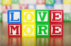 Älska mer stavad ut i alfabetbyggnadsblock Arkivbild