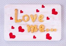 Älska mig textdanande med hemlagade kakor på en trätabell för Arkivbild