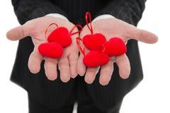 älska min take Händer som rymmer röda hjärtor Manligt öppet gömma i handflatan med förälskelsesymbolslut upp Förälskelse- och val royaltyfria bilder