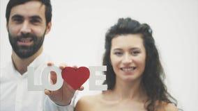 Älska mjuka par på vit bakgrund allvarligt folk En söt kvinna med hennes make rymmer ett träord för förälskelse in