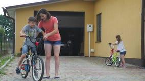Älska modern hjälp hennes gulliga son att rida en cykel stock video