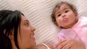Älska modern med behandla som ett barn i säng arkivfilmer