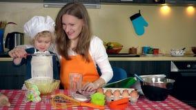 Älska modern med hennes upphetsade gulliga dotterflicka som siktar mjöl i kök stock video