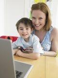 Älska modern och sonen med bärbar datorsammanträde på tabellen Arkivfoton