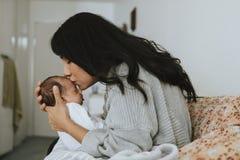 Älska modern som kysser hennes spädbarn, behandla som ett barn royaltyfria bilder
