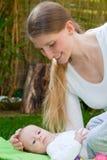 Älska modern som spelar med henne, behandla som ett barn i trädgården arkivfoton