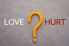 Älska och göra ont begreppet med text- och frågefläcken Arkivbilder
