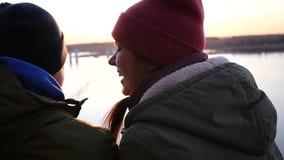 Älska och lyckligt parsammanträde på flodbanken som ler på de mot solnedgångbakgrunden långsam rörelse lager videofilmer