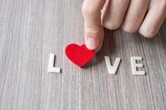 ÄLSKA ordet av träalfabetbokstäver med kvinnahanden som rymmer röd hjärtaform på tabellbakgrund Romans, romantiker och valentin arkivbilder