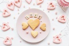 ÄLSKA ordet, och hjärta formade kakor på en rosa platta arkivbild
