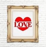 Älska ordet och hjärtasymbolen (som säger förälskelse) i den guld- tappningfotoramen på den vita tegelstenväggen, förälskelsebegr Royaltyfria Foton