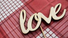 Älska ordet Älska träbokstäverna på den röda rutiga servetten