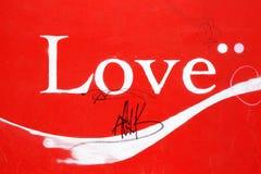 Älska ordteckenbakgrund mot en röd vägg arkivfoton