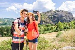 Älska par av fotvandrare som tar en selfie på semester royaltyfri foto