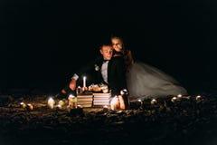 Älska par dela en romantisk matställe med stearinljus och kakan på stranden, kust mot underbar natt Arkivfoton