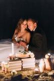 Älska par dela en romantisk matställe med stearinljus och kakan på stranden, kust mot underbar natt Arkivbilder