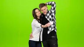 Älska par flörtar till varandra och gör selfies grön skärm stock video