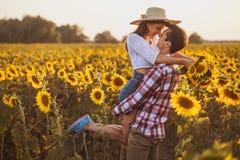 Älska par i ett blommande solrosfält royaltyfria foton