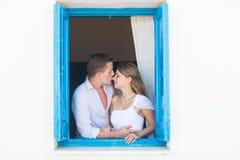 Älska par i fönstret Arkivfoton