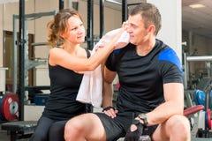 Älska par i idrottshallen som vilar efter sport Fotografering för Bildbyråer