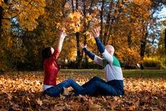Älska par kasta sidorna i Autumn Park arkivfoto