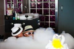 Älska par ligg i ett badrum med bad-skum. Arkivbild