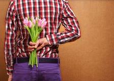 Älska par - man med blommor som väntar hans kvinna. Arkivbilder