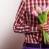 Älska par - man med blommor som väntar hans kvinna. Arkivfoto