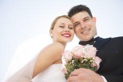 Älska par med blommabuketten mot klar himmel Royaltyfria Bilder