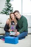 Älska par med julgåvor hemma Royaltyfria Bilder