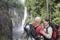 Älska par med ryggsäckar mot vattenfallet Arkivbild