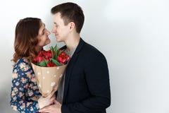 Älska par med tulpanbuketten, vit bakgrund Arkivfoto