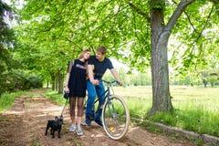 Älska par på cykeln med hunden i parkera Arkivbilder