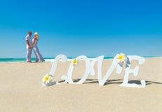 Älska par på den sandiga stranden för det tropiska havet med förälskelse uttrycka dekoren Arkivbild
